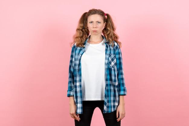 Giovane donna di vista frontale in camicia a scacchi blu con espressione triste su sfondo rosa donna emozioni modello moda ragazze colore
