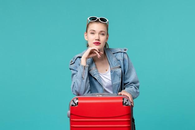 Giovane femmina di vista frontale in giacca blu che si prepara per il viaggio sullo spazio blu