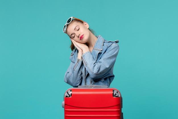 Giovane donna di vista frontale in giacca blu che si prepara per il viaggio e sensazione di stanchezza sullo spazio blu
