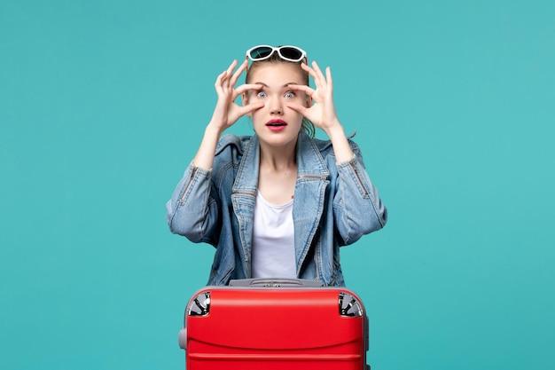 Giovane femmina di vista frontale in giacca blu che si prepara per il viaggio aprendo gli occhi sullo spazio blu