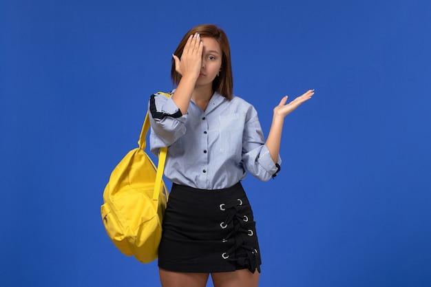 Vista frontale della giovane donna in camicia blu gonna nera che indossa uno zaino giallo chiudendo metà del suo viso sulla parete blu