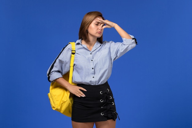 Front view of young female in blue shirt black skirt wearing yellow backpack shutting her nose on light blue wall