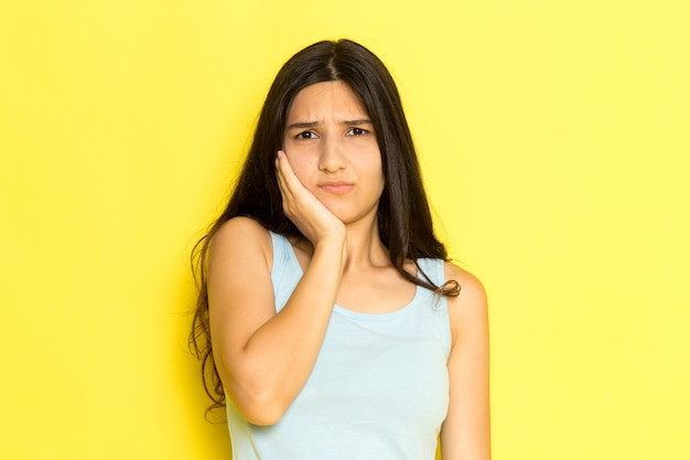 A front view young female in blue shirt having a toothache on the yellow background girl pose model beauty young
