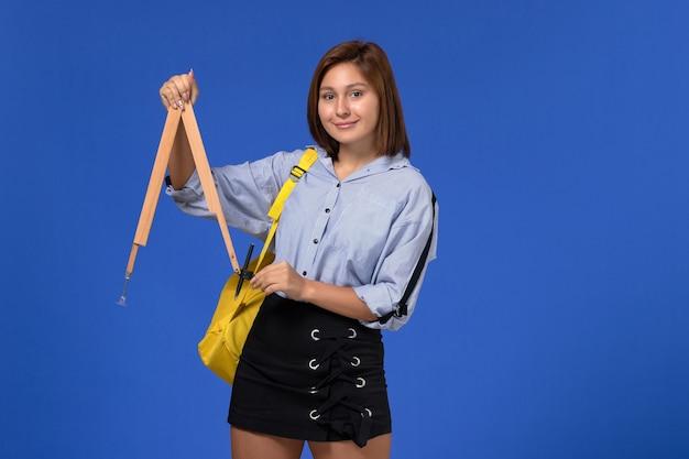 Vista frontale della giovane donna in camicia blu che tiene la figura di legno sulla parete blu