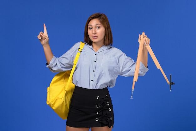 Vista frontale della giovane donna in camicia blu che tiene la figura di legno sulla parete azzurra