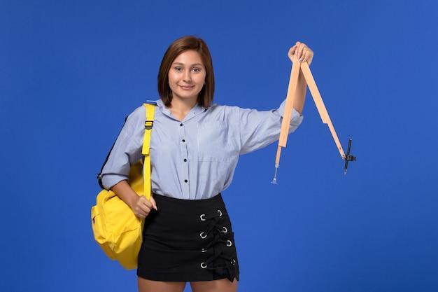Vista frontale della giovane donna in camicia blu che tiene la figura di legno sorridente sulla parete blu