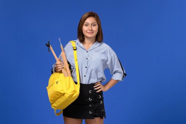 Vista frontale della giovane donna in camicia blu che tiene la figura di legno sorridente sulla parete blu-chiaro