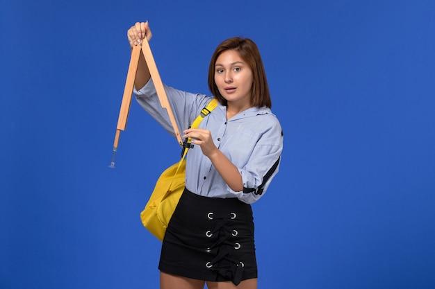 Vista frontale della giovane donna in camicia blu che tiene il modulo di legno sulla parete blu