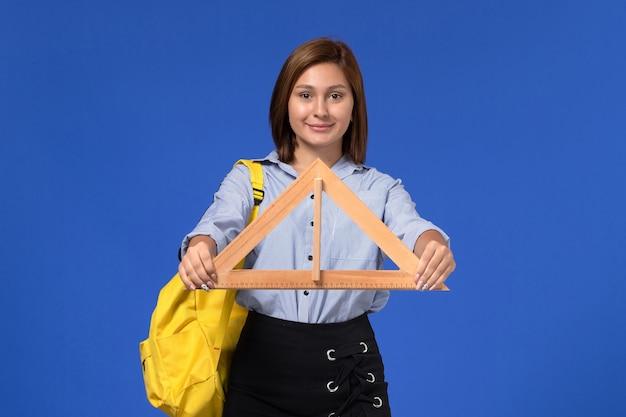 Vista frontale della giovane donna in camicia blu che tiene un triangolo di legno sorridente sulla parete blu