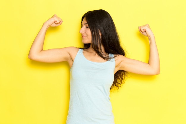 A front view young female in blue shirt posing and flexing with smile on the yellow background girl pose model beauty young