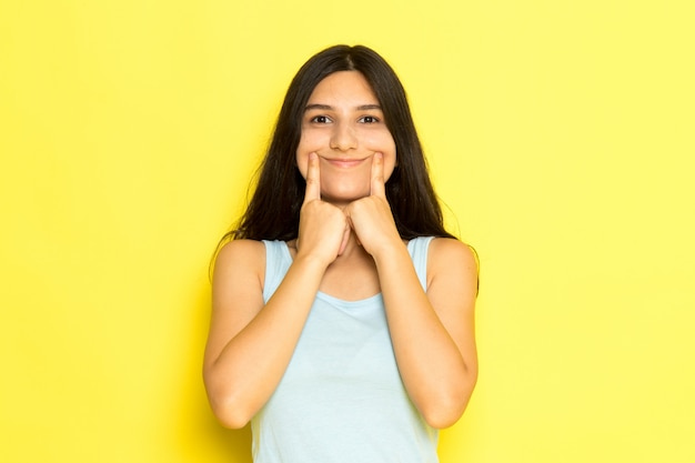 A front view young female in blue shirt posing holding her mouth making a smile