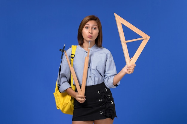 Vista frontale della giovane donna in camicia blu che indossa uno zaino giallo che tiene figure di legno sulla parete blu-chiaro