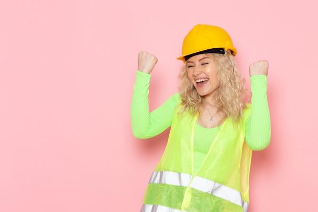 Giovane costruttore femminile di vista frontale nell'espressione felice del casco verde del vestito della costruzione sui lavori di costruzione rosa di architettura dello spazio