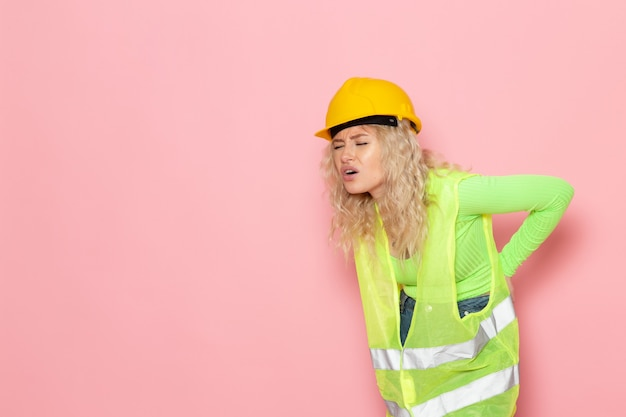 Front view young female builder in green construction suit helmet having a back ache on the pink space architecture construction job work lady