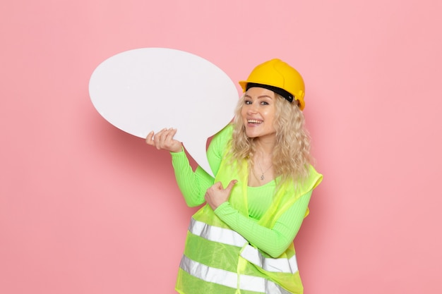 Front view young female builder in green construction suit helmet holding a big white sign on the pink space architecture construction work
