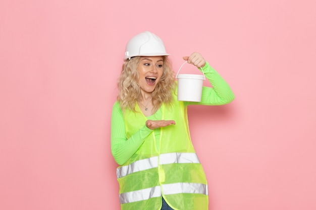 Front view young female builder in green construction suit helmet holding a paint on the pink space architecture construction work
