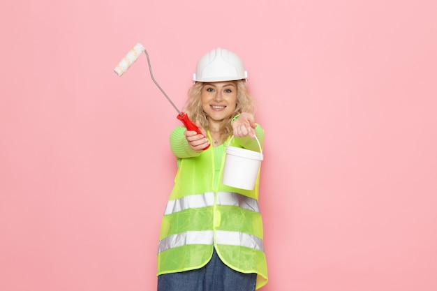 Front view young female builder in green construction suit helmet holding paints and brush on the pink space