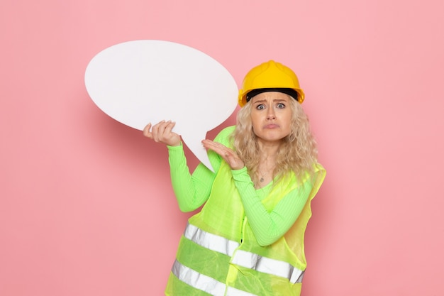Front view young female builder in green construction suit helmet holding white sign on the pink space  job