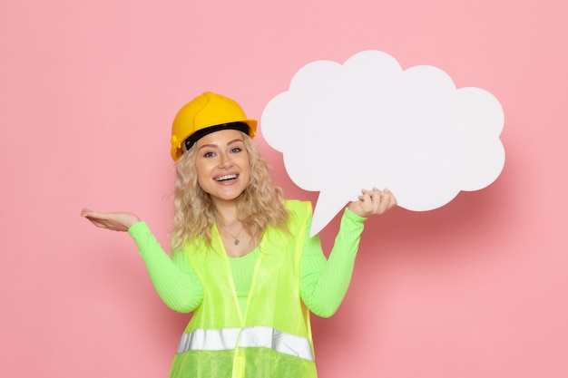 Front view young female builder in green construction suit helmet holding white sign with smiles on the pink space architecture construction job work lady