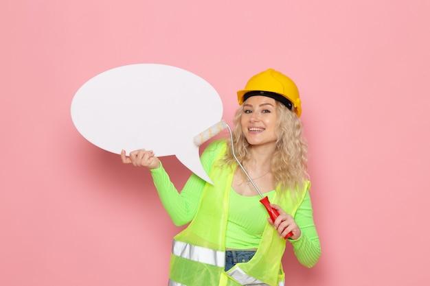 Giovane costruttore femminile di vista frontale in casco verde del vestito della costruzione che posa con il segno bianco con un leggero sorriso sulla signora del lavoro di lavoro di costruzione di architettura dello spazio rosa