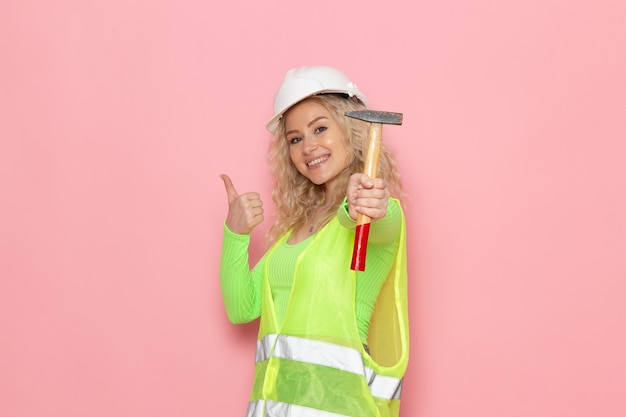 Front view young female builder in green construction suit helmet smiling and holding hammer on the pink space