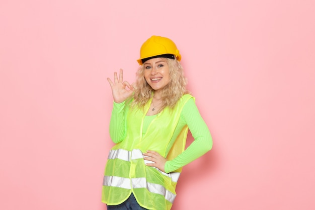 Giovane costruttore femminile di vista frontale nel casco verde del vestito della costruzione che sorride e che posa sulla signora rosa del lavoro di costruzione di architettura dello spazio