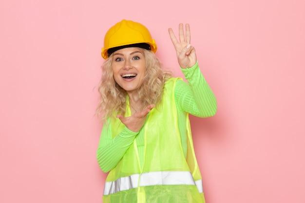 Giovane costruttore femminile di vista frontale nel casco verde del vestito della costruzione che sorride e che mostra il segno di vittoria sulla signora rosa del lavoro di costruzione di architettura dello spazio