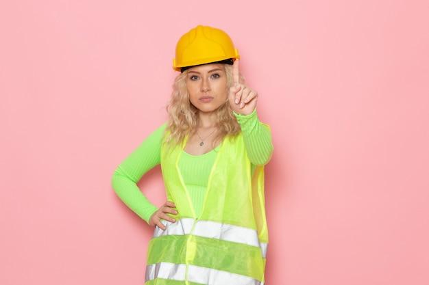 Giovane costruttore femminile di vista frontale nell'avvertimento verde del casco del vestito della costruzione con il dito sulla signora del lavoro di lavoro di costruzione di architettura dello spazio rosa