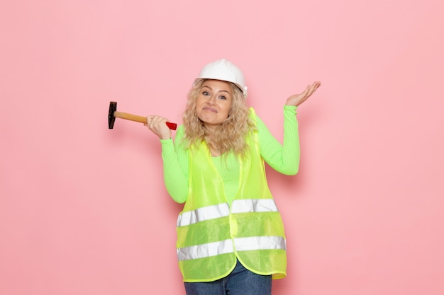 Front view young female builder in green construction suit yellow helmet holding hammer on the pink space job architecture construction job