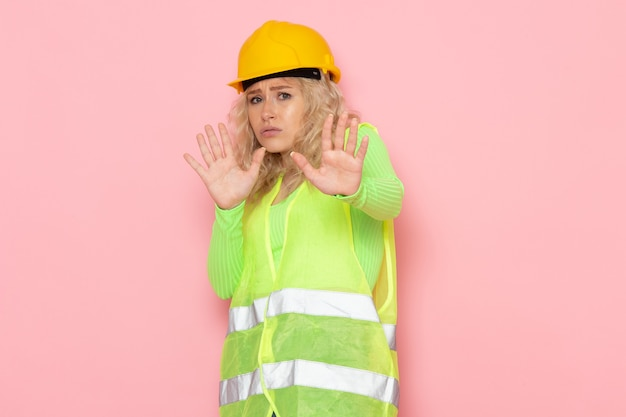 Front view young female builder in green construction suit yellow helmet posing with caution on the pink space job architecture construction  photo