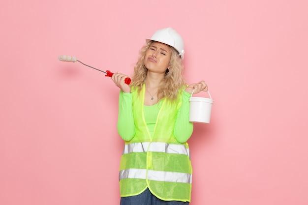 緑の建設スーツヘルメットを保持している正面の若い女性ビルダーブラシとピンクの空間建築建設作業にペイント