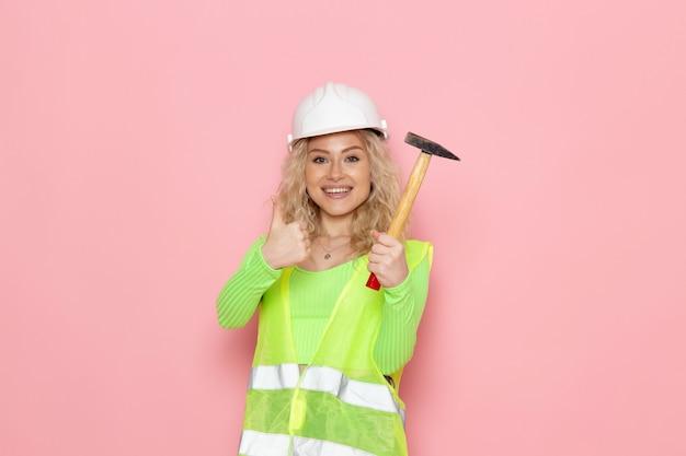 Вид спереди молодая женщина-строитель в зеленом строительном шлеме с молотком, улыбаясь в розовом пространстве