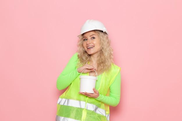 ピンクのスペースに白いペンキを保持している緑の建設スーツヘルメットの正面若い女性ビルダー