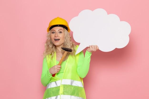 ピンクのスペースにハンマーと一緒に白い看板を持っている緑の建設スーツヘルメットの正面の若い女性ビルダー