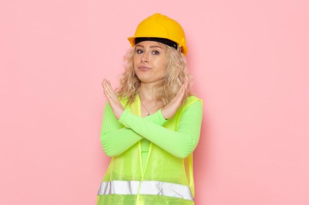 ピンクのスペース建築工事の禁止標識を示す緑の建設スーツヘルメットで正面の若い女性ビルダー
