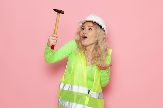 ピンクの空間建築建設の仕事にハンマーを保持している緑の建設スーツの白いヘルメットで正面の若い女性ビルダー