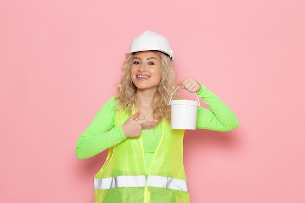 Вид спереди молодая женщина-строитель в зеленом строительном костюме с белым шлемом, держащая пластиковую банку с улыбкой на розовом пространстве, работа, архитектура, строительство