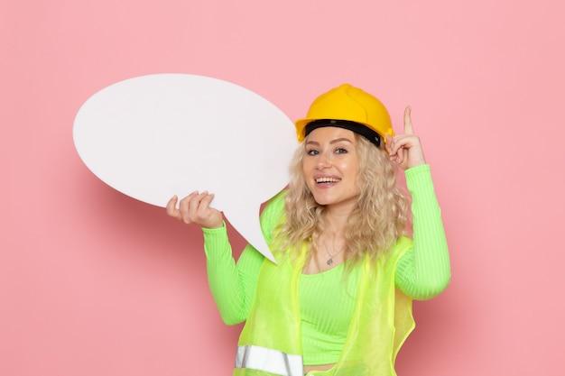 ピンクのスペースジョブアーキテクチャ建設写真に大きな白い看板を持っている緑の建設スーツ黄色いヘルメットの正面の若い女性ビルダー
