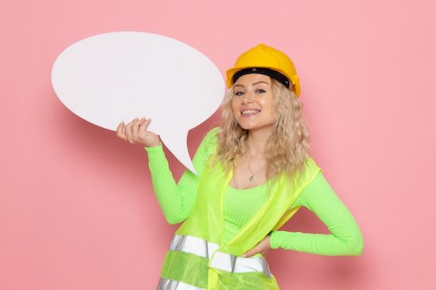 Вид спереди молодая женщина-строитель в зеленом строительном костюме в желтом шлеме с большим белым знаком, улыбаясь в розовом пространстве, работа, архитектура, строительство
