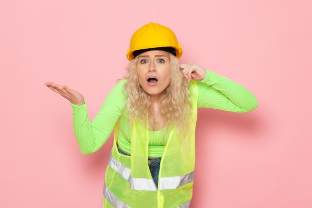 Вид спереди молодая женщина-строитель в зеленом строительном костюме с желтым шлемом позирует на розовом пространстве