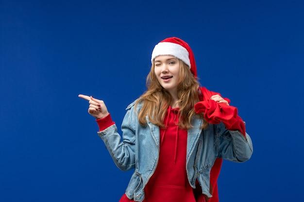 青い床の色の感情のクリスマスのプレゼントでいっぱいの正面図若い女性のキャリングバッグ
