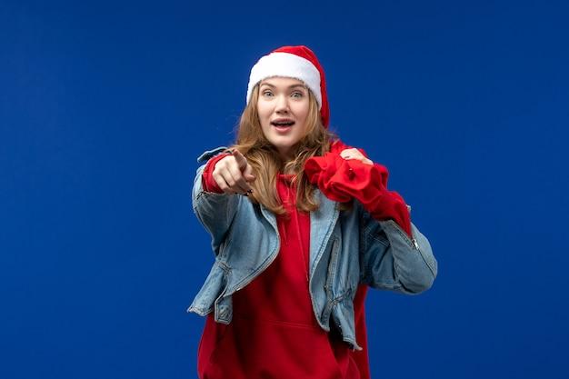 Vista frontale giovane donna borsa da trasporto piena di regali sullo spazio blu