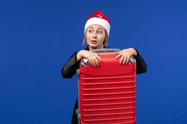 Вид спереди молодая женщина, несущая тяжелую сумку на синей стене, отпуск женщина, праздники