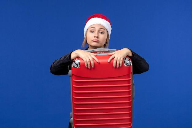 Giovane donna di vista frontale che trasporta borsa rossa pesante sulla vacanza della donna di vacanza dello scrittorio blu