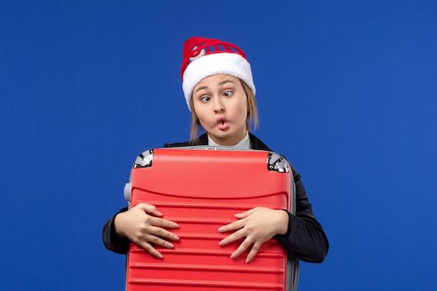 Giovane donna di vista frontale che trasporta borsa rossa pesante sulla vacanza della donna di vacanza della parete blu
