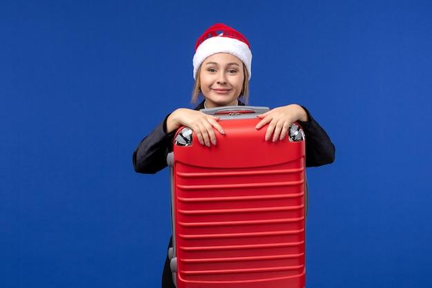 Вид спереди молодая женщина, несущая тяжелую красную сумку на синем полу, отпуск женщина, отдых