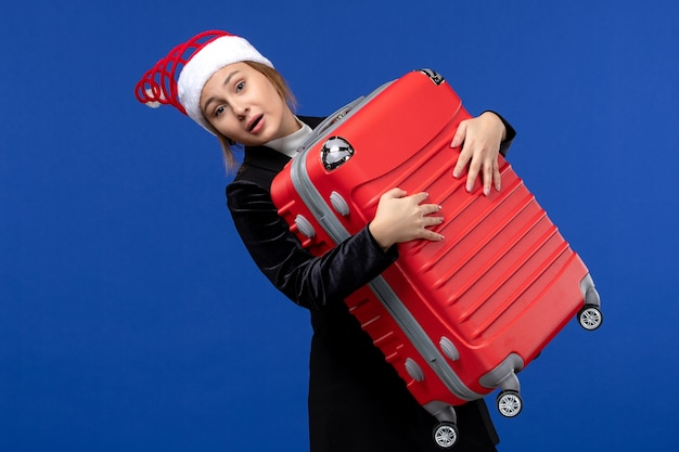 Вид спереди молодая женщина, несущая тяжелую красную сумку на синей стене, отпуск женщина, праздник