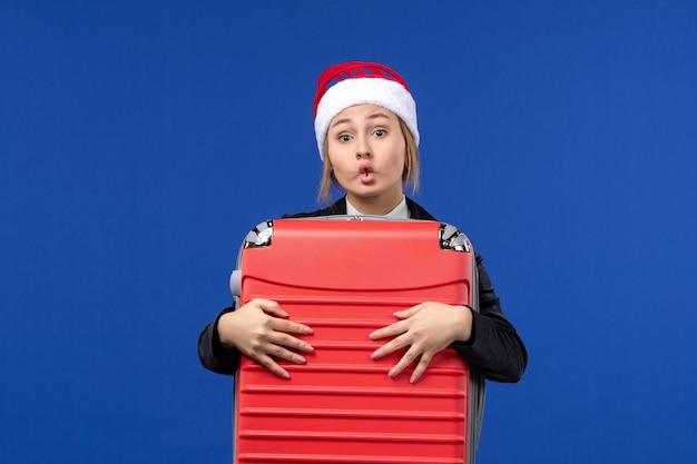 Вид спереди молодая женщина, несущая тяжелую красную сумку на синей стене, отпуск, женщина, отдых