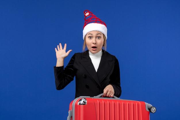 青い壁の休日の休暇の女性に彼女の大きな赤いバッグを運ぶ正面図若い女性