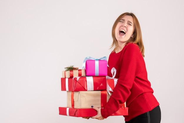 Вид спереди молодая женщина, несущая подарки